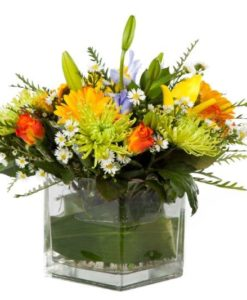 Mixed seasonal flowers in square glass vase
